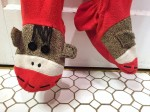 Close up of sock monkey decoration on feet of adult footie pajamas by Nick and Nore