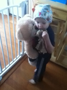 Toddler hugging a teddy bear in front of The First Years Hands Free Baby Gate