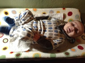 Baby laying on changing pad liner on top of contoured changing pad