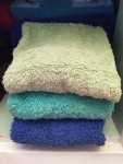 Stack of folded hand towels in green, turquoise, and blue folded in linen closet