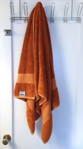 Pinzon bamboo cotton blend bath towel in orange hanging from hook on back of bathroom door