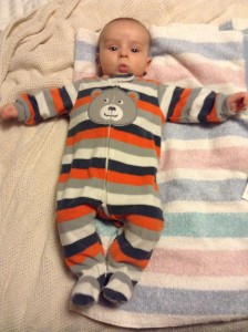 Infant in striped pajamas laying on striped towel