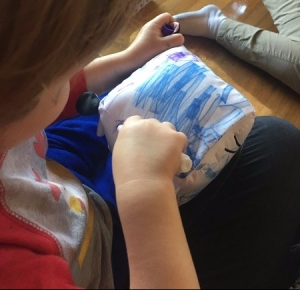 Preschooler coloring on Doodlemals stuffed animal with crayola markers