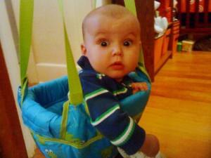 Surprised infant in Johnny Jump Up doorway jumper