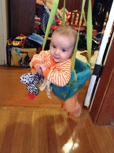 Infant holding toy in Johnny Jump Up doorway jumper