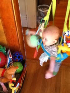 Infant playing in Johnny Jump Up doorway jumper near a bin of toys