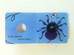Little Spider finger puppet board book open to blue page spread with hole for puppet
