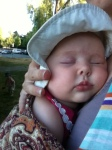 Infant sleeping in sun hat carried in ring sling