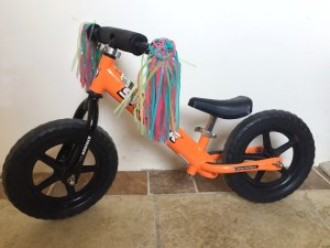 Strider balance bike in orange with pink green and blue handlebar streamers