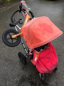 Strider orange balance bike loaded onto Bugaboo Frog stroller