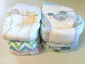 Two stacks of disposable diapers shown side by side from Honest company and huggies brands