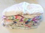 a stack of disposable diapers from Honest company and huggies brands