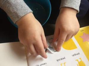 Child attaching sticker to activity book