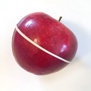 Sliced apple with rubber band holding it together in apple shape