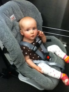 Infant riding in car seat wearing baby leg warmers