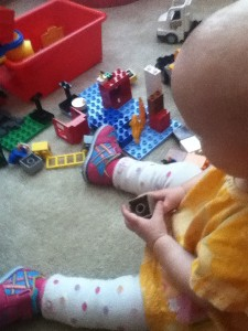 Infant playing with toys while wearing baby leg warmers