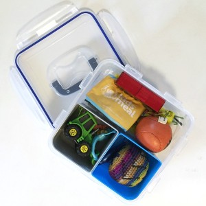 Clear square container packed with small toys for long car ride