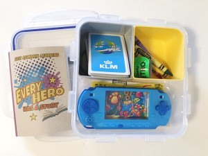 Busy box for kids with deck of cards, crayons, small notebook, slap bracelet, and handheld game inside compartments