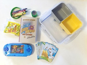 Clear plastic square container with removable colored nesting containers and toys for car ride