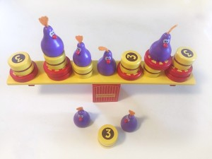 Chicky boom balancing game set up with three pieces removed from yellow beam