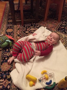 Infant in red striped pajamas lying on floor on top of towel with toys around
