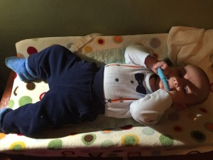 Infant boy chewing on teething ring while lying on changing table
