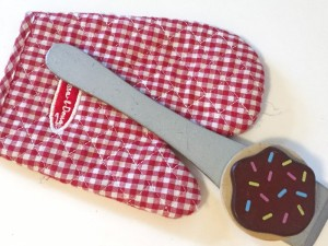 Oven mitt, wooden silver spatula and cookie with chocolate frosting and sprinkles from Melissa and Doug wooden slice and bake cookie set