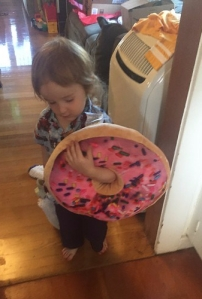 Toddler carrying a donut pillow pink frosting sprinkles with arm through hole in middle
