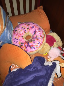 Donut pillow with pink frosting and sprinkles in toddler bed with other pillows, stuffed animals, and blankets