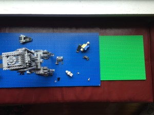 Lego brand square green base plate next to blue long double sided base plate