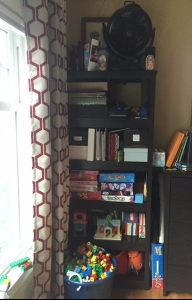 72 inch black bookshelf holding toys, games, and books
