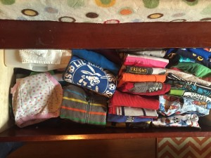 Child's shirts folded and stored vertically upright in dresser drawer
