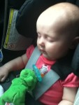 Infant sleeping in car seat on airplane with wubbanub soothie pacifier resting on chest