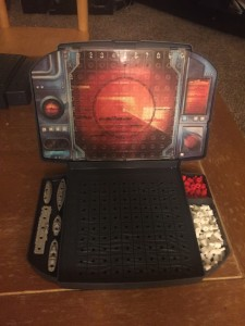 Battleship game board opened with ships and pegs to record hits and misses stored