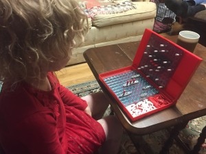 Five year old child playing battleship on classic red board