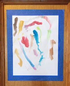 Three year old's painting framed and stuck to wall with blue painters tape