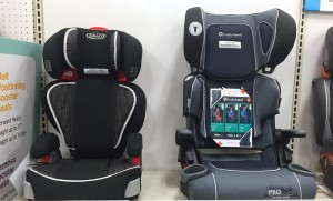 Two belt positioning booster seats side by side on a shelf by Graco and Babytrend