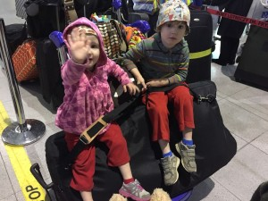 Toddler and preschooler sitting on pile of luggage at airport