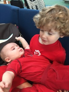 Child holding baby wearing red shirts