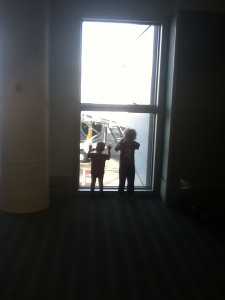 Kids silhouetted by window at airport