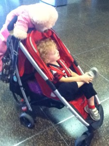 Stroller loaded with stuff for travel including toddler