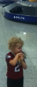 Toddler wearing football jersey in front of baggage claim at airport
