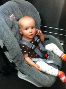 Infant wearing baby legs riding in car seat on wheels through airport