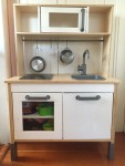 IKEA Duktig play kitchen filled with kitchen toys and pots and pans