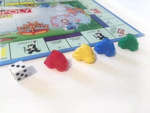 Red, yellow, blue, and green car game pieces to move around the Monopoly Junior board