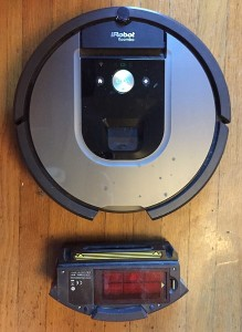 Roomab robotic vacuum with collection tray removed nearby