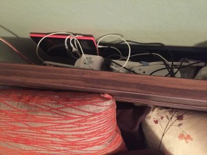 Picture ledge shelf installed behind headboard to keep electronics and reading lamps as seen from above