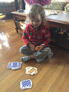Three year old playing Slamwich card game on floor