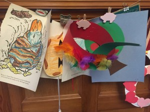 Coloring pages, hat, and glueing projects displayed on wall