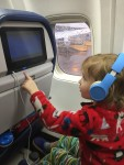 Preschooler wearing blue kids headphones on board airplane adjusting seatback screen entertainment